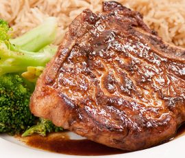 Grilled pork chops served with rice and broccoli