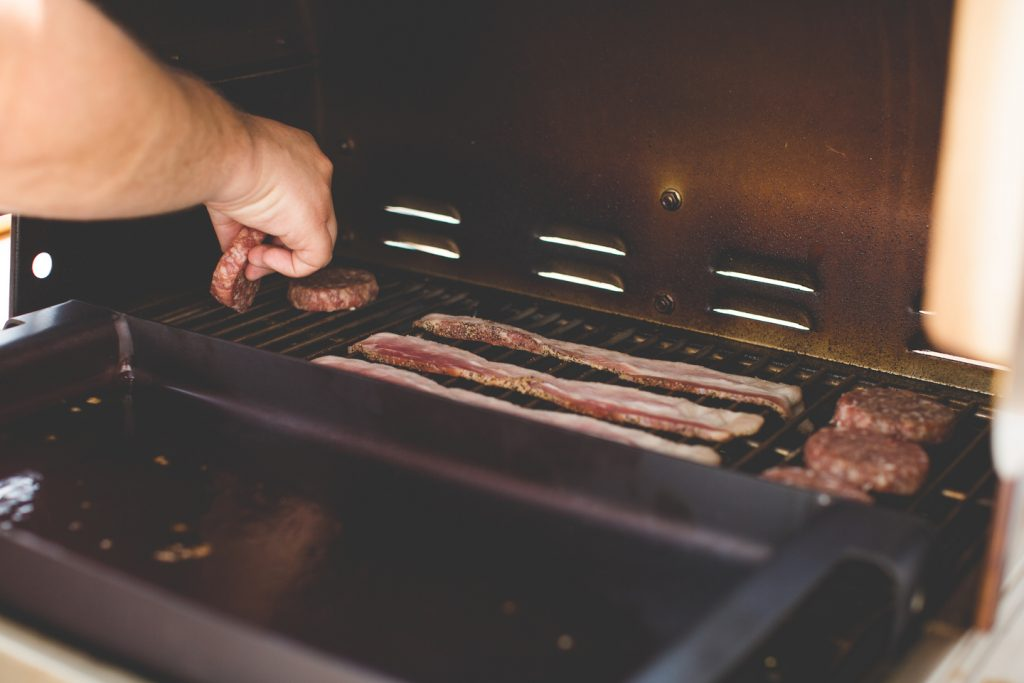 Placing breakfast sausage and bacon on the MAK pellet grill