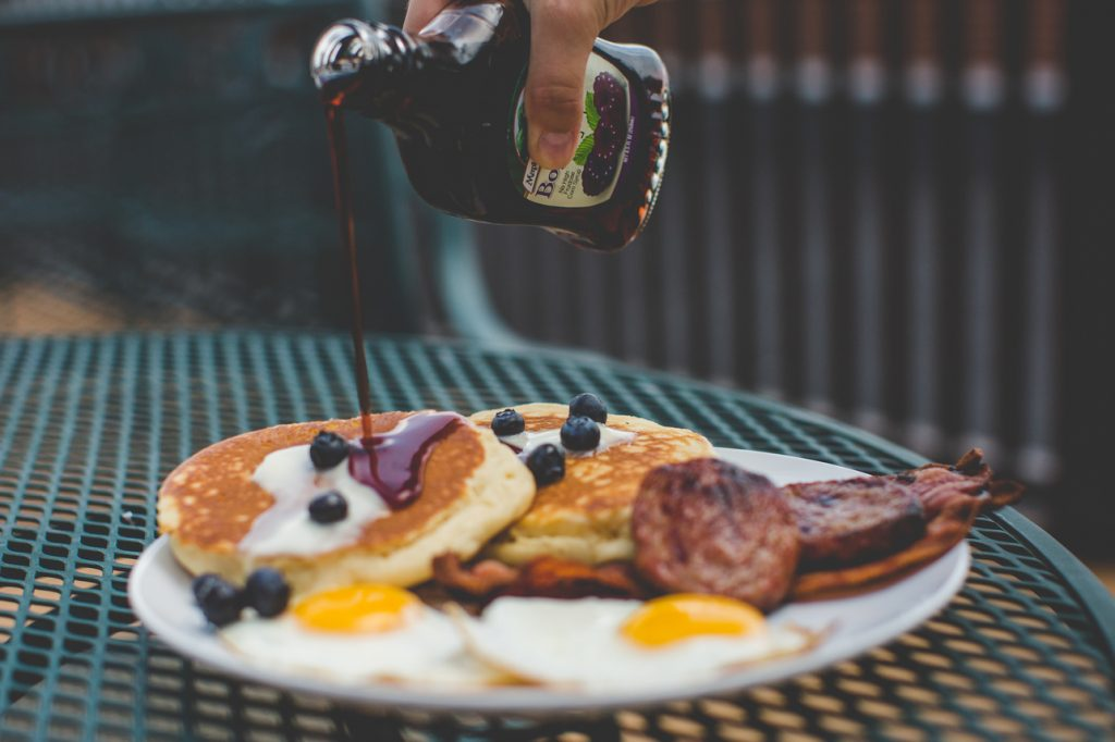 Pouring syrup onto pancakes with butter and berries with eggs and breakfast meats on the side